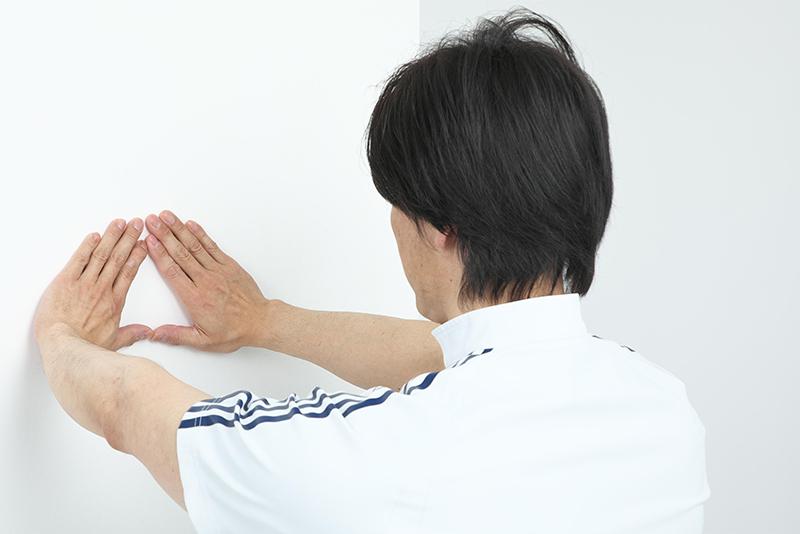 カベに両手を三角にするように手をついている