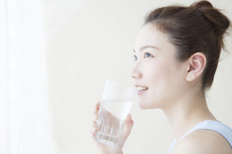 水の入ったグラスを片手に微笑む女性