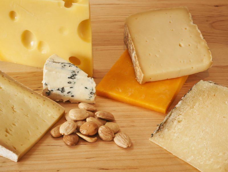 さまざまな種類のチーズとアーモンドがカッティングボードにならんでいる