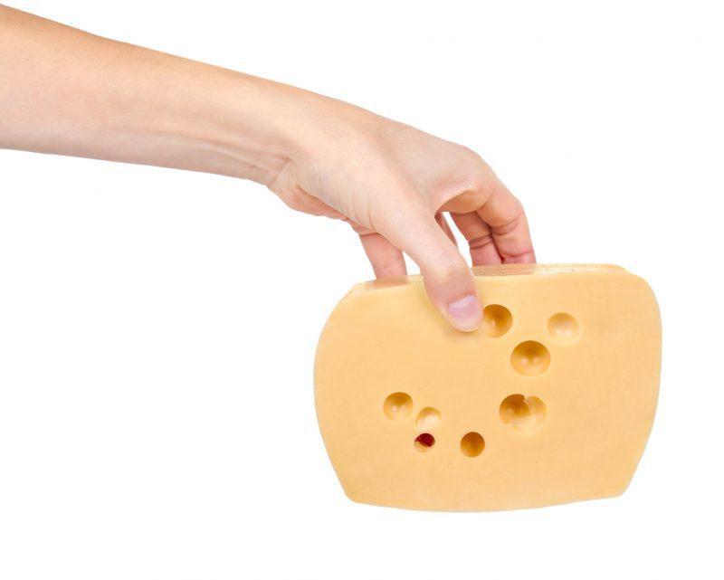 ナチュラルチーズを持ち上げながら健康的な爪を見せている
