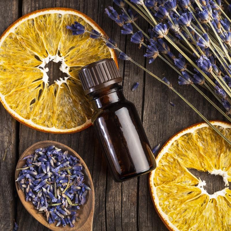アロマオイルの瓶と乾燥した輪切りのオレンジとラベンダー