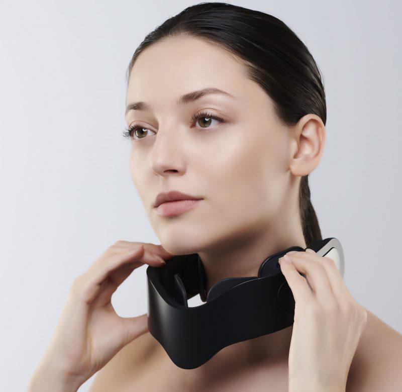 ヤーマン『メディリフト ネック』を首に装着しようとしている女性
