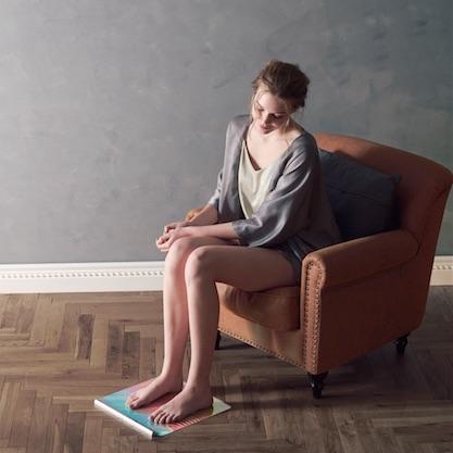 アテックス『ルルドスタイル EMSシート』に足をのせ、ソファに腰掛けている女性