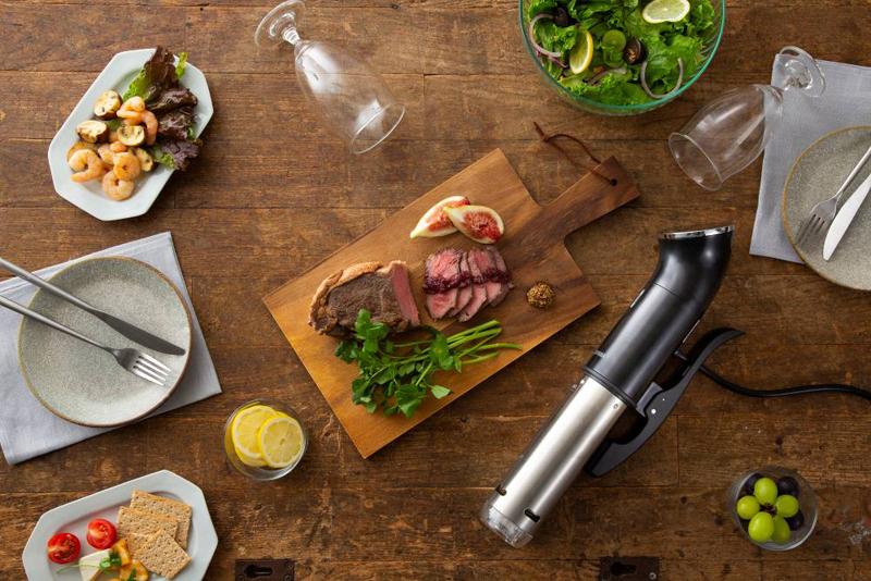 サラダやローストビーフ、グラス、低温調理器などがセッティングされたテーブル