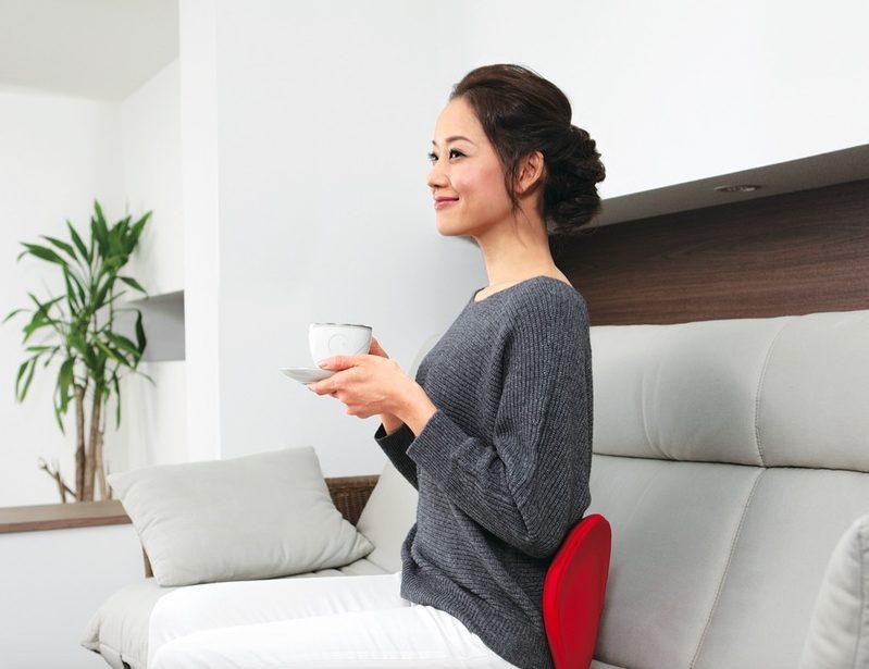 ソファの上にMTGのボディメイクシートスタイルを置いてそこに座ってくつろいでいる女性