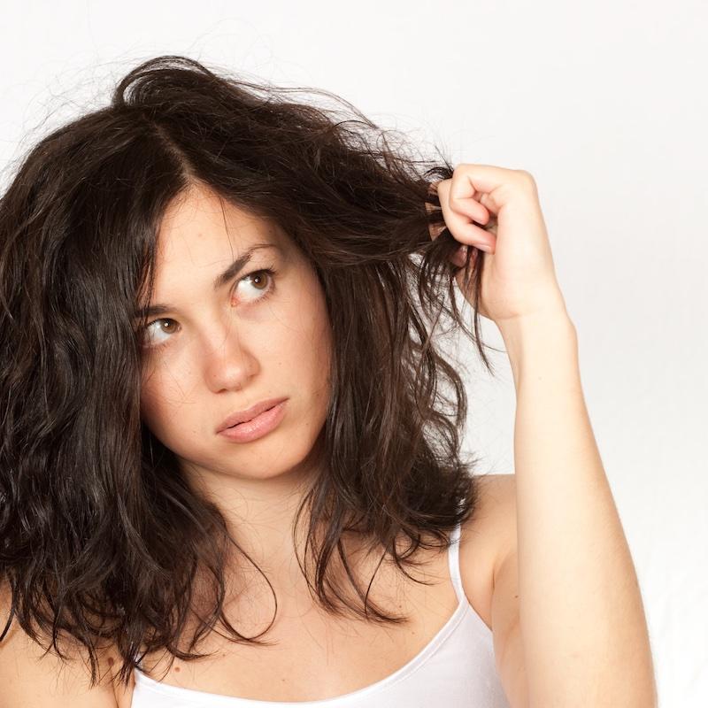 くせ毛を掴んでいる女性