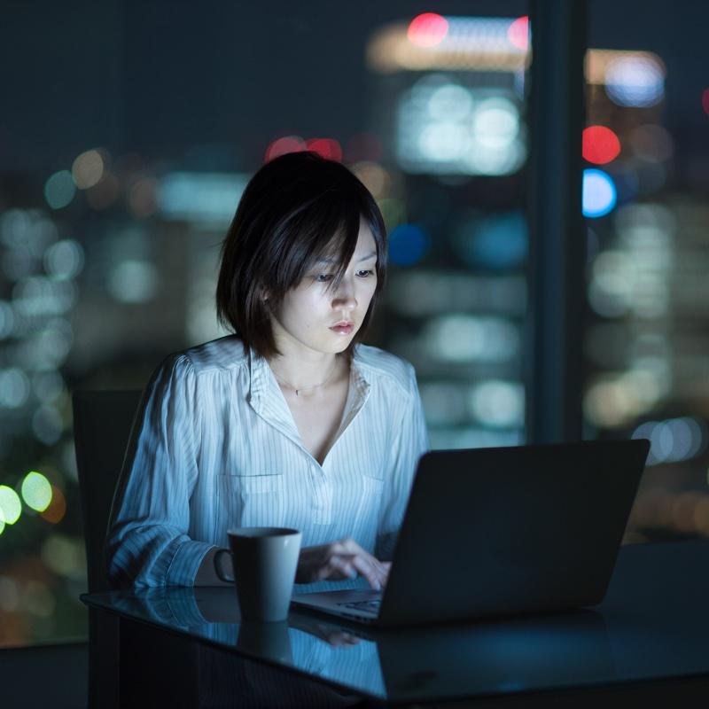 夜にパソコンを使っている女性
