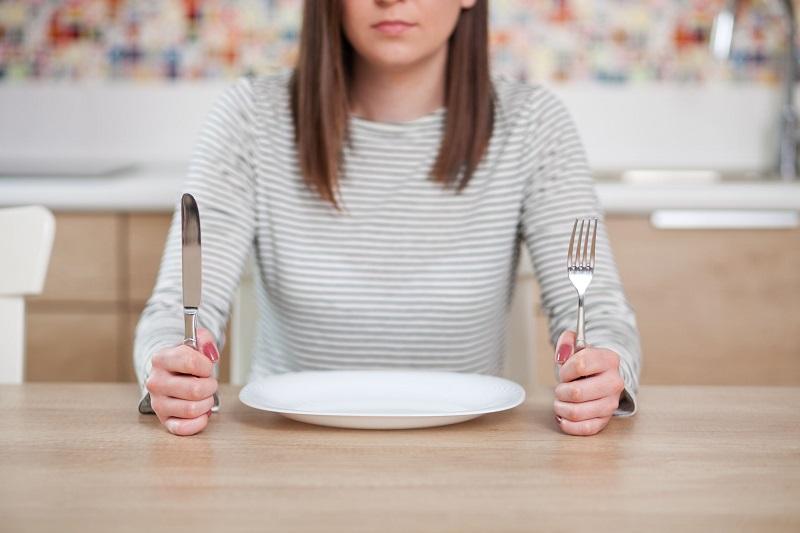 食卓の空のお皿とフォークとナイフを持った女性の画像