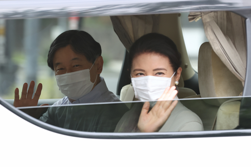 天皇陛下と雅子さまがお車にのって沿道に手を振っている