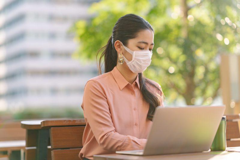 屋外でパソコンに打ち込むマスク姿の女性