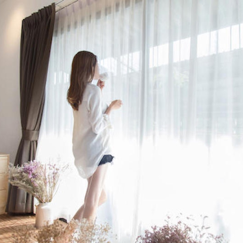 カーテンから差し込む日光に当たる女性
