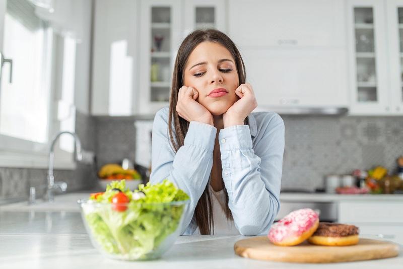 サラダとドーナツを前にして悩む女性