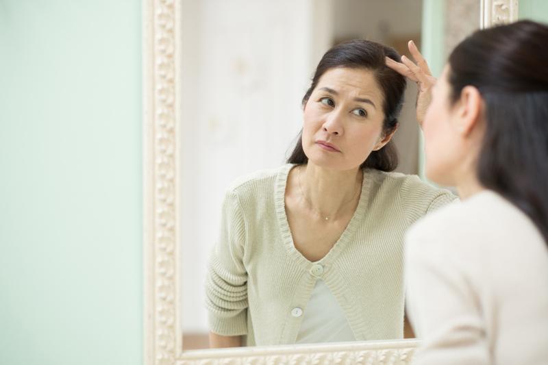 鏡を見ながら分け目を気にする中年女性の写真