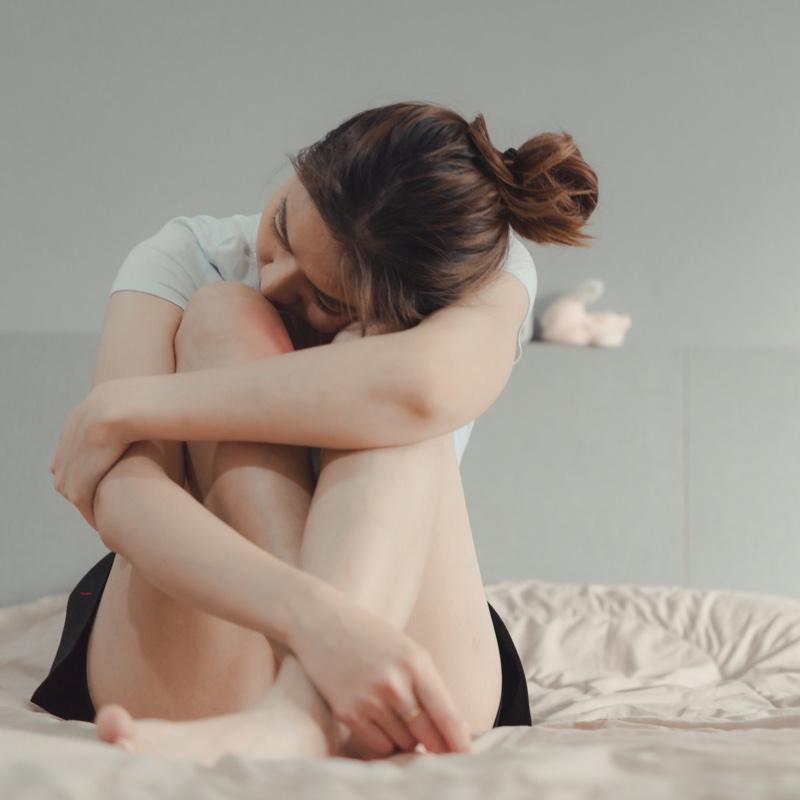 ベッドの上でうずくまる女性