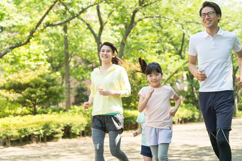 ランニングをする若い夫婦と2人の子供
