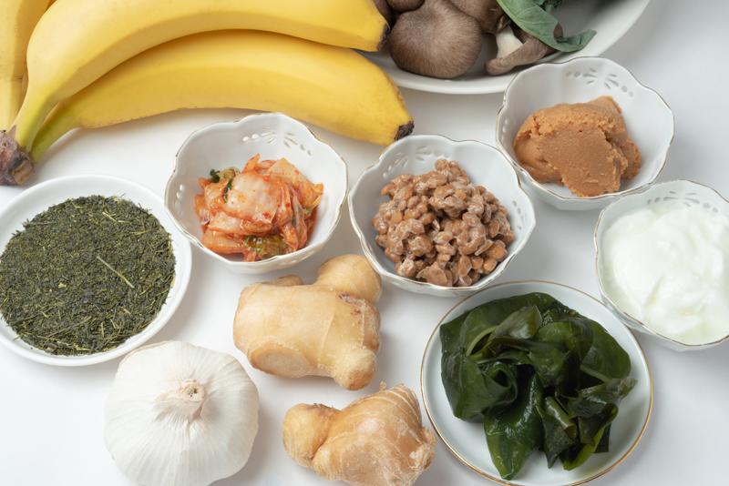 テーブルに乗せたバナナ、緑茶、キムチ、納豆、みそ、ヨーグルト、わかめ、しょうが、にんにく画像