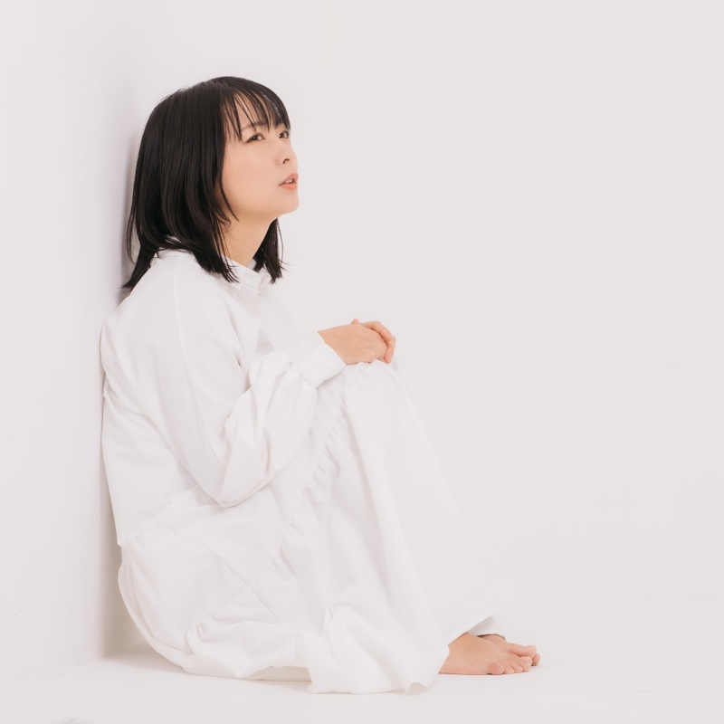 壁に寄りかかって座る女性