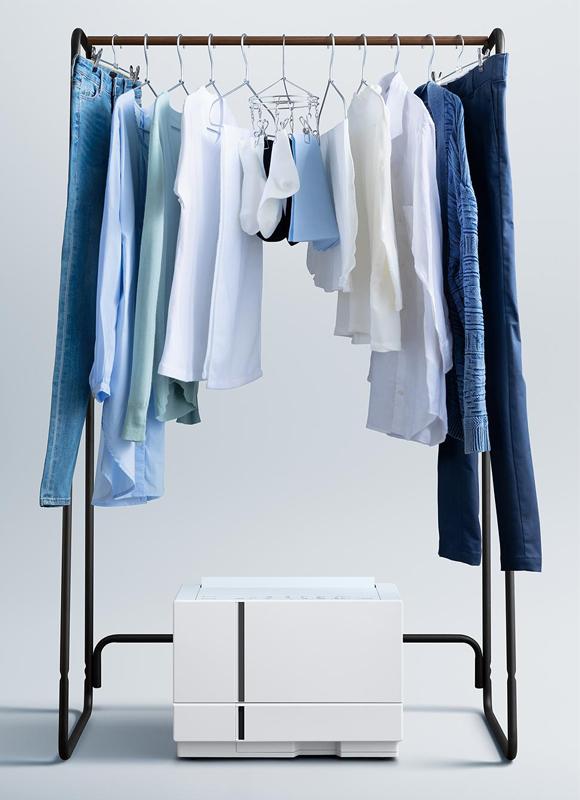 部屋干しをする衣類の下に衣類乾燥除湿機が置かれている