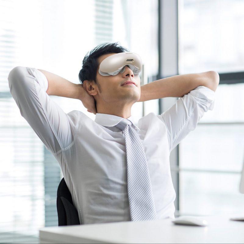 パナソニックの目もとエステ EH-SW68を装着してオフィスの机でくつろぐ男性