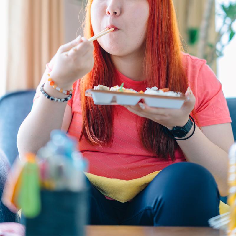 ソファに座ってお弁当を食べる女性