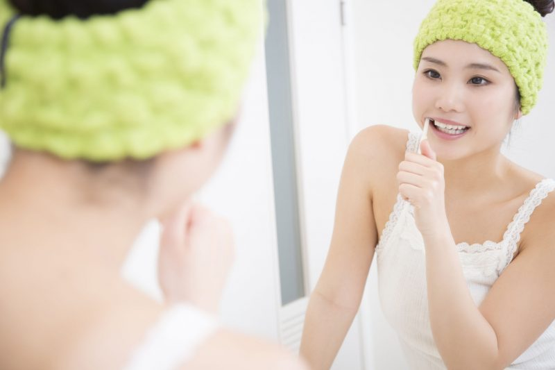 鏡を見ながら歯磨きする女性