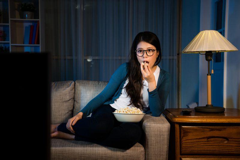暗い部屋でソファに座ってポップコーンを手にテレビを見る女性