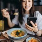 スマホを見ながら食事する女性