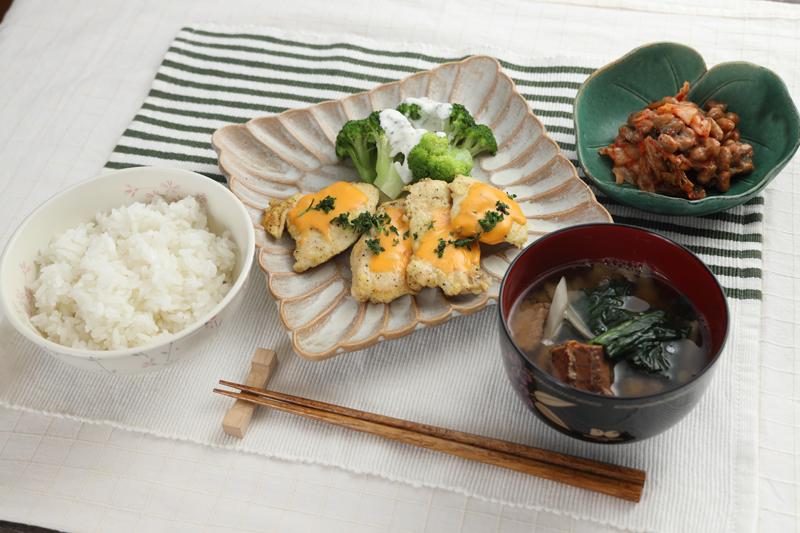 白米、さば缶とほうれん草とごぼうのみそ汁、チキンのチーズ焼き、ブロッコリーのヨーグルトソースがけ、キムチ納豆がテーブルに並んでいる