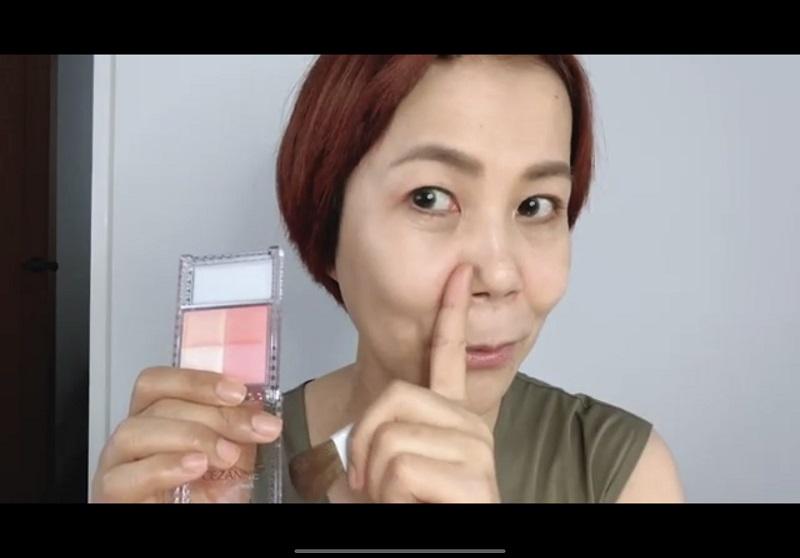 小鼻の横に人差し指を当てる山本浩未さん