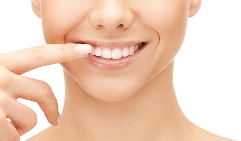 笑顔で歯を指さす女性の口元