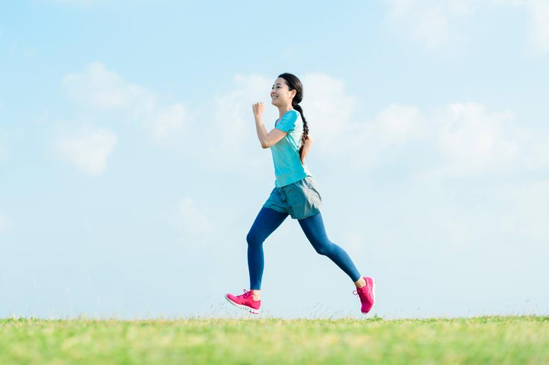 笑顔で飛び跳ねるようにランニングする女性