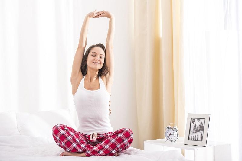 ベッドであぐらをかいて伸びをする女性