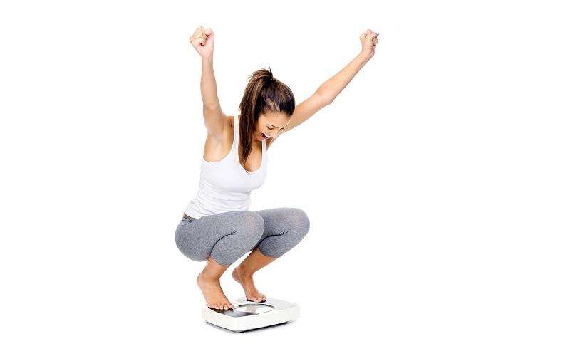体重計に乗って、両手を挙げて喜ぶ女性
