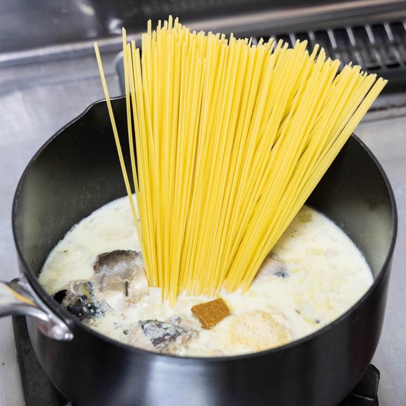 豆乳、コンソメ、パスタ、粉チーズがサバ缶と玉ねぎを炒めた鍋に入っている