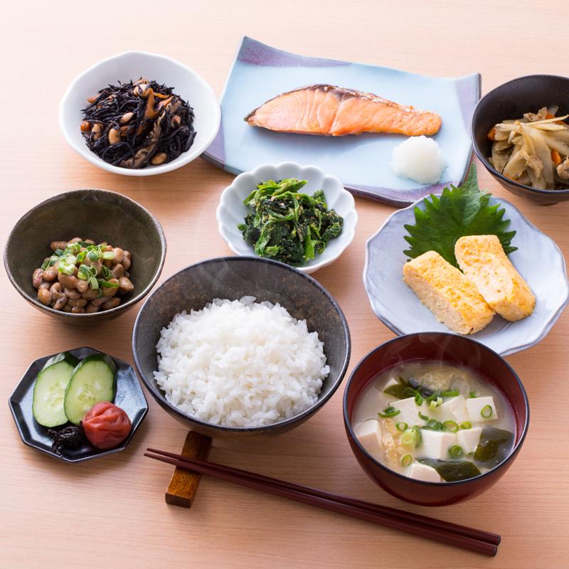 ごはんやみそ汁、焼き魚などの和食がテーブルに並んでいる