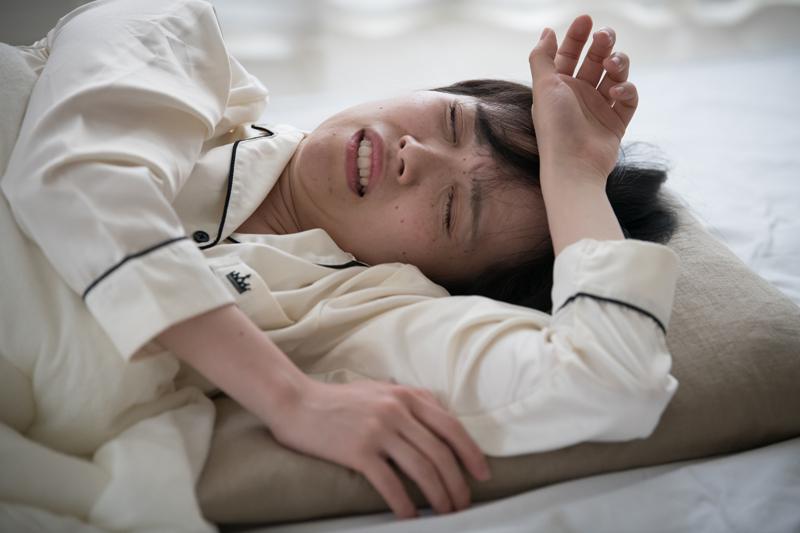 寝不足ぎみにベッドで横になっている女性