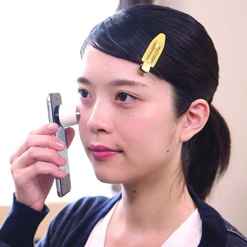 スマホにガジェットジャパン 『NOFL Smart(ノーフルスマート)』をつけて顔に当てる女性