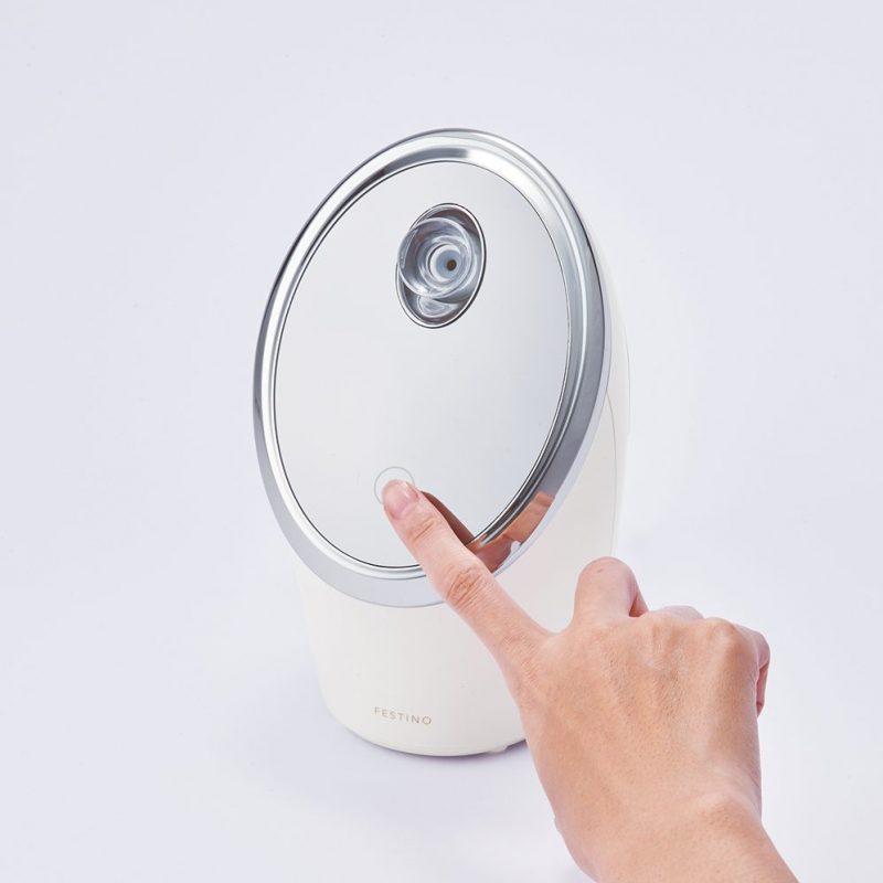 シンプルマインド FESTINO『フェイシャル モイスト ナノスチーマー』のスイッチを入れている手元