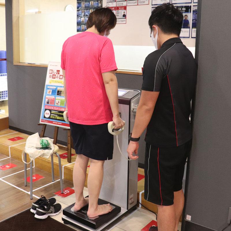 コナミスポーツクラブのインストラクター横田昌佳さんが見守る中、体重を測るライターM