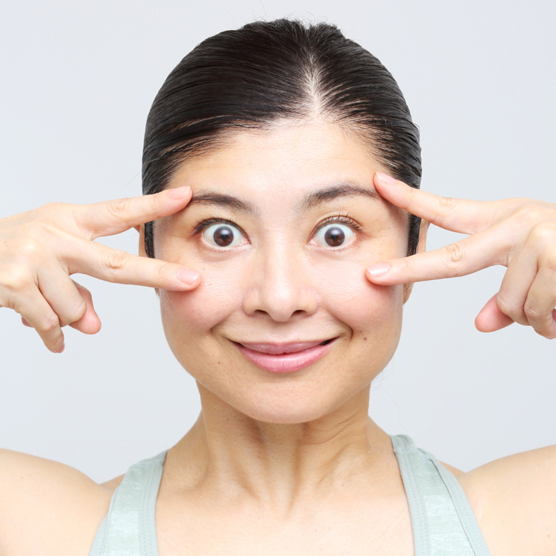 人さし指と中指でV字を作り、目の上下を挟んでまぶたを引き上げ目を大きく開いた間々田さん