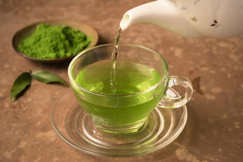ガラスのカップに緑茶を注いでいる写真