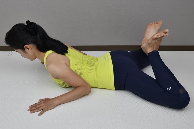うつ伏せになり左右のかかとをつけ、ひざは外に開き腕は胸の横においた姿の女性