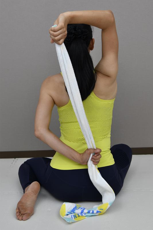 横座りの状態でタオルを背中の後ろで持った女性