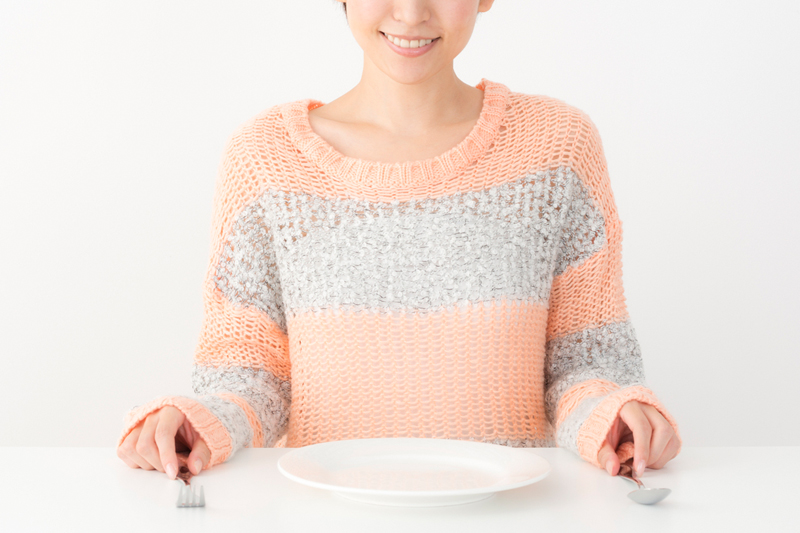 空の皿を前に断食を決意する女性