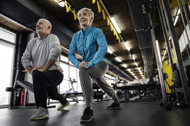 ジムでストレッチをする太った高齢男性と細身の高齢女性