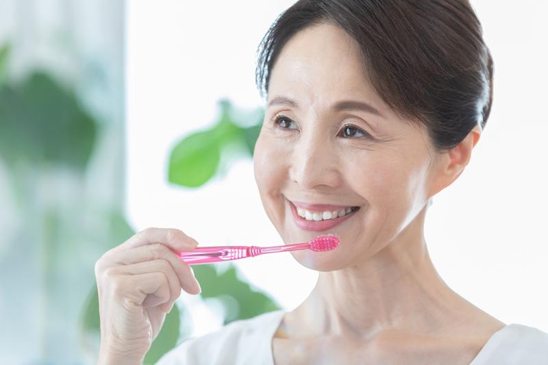 歯ブラシをてに笑顔の女性