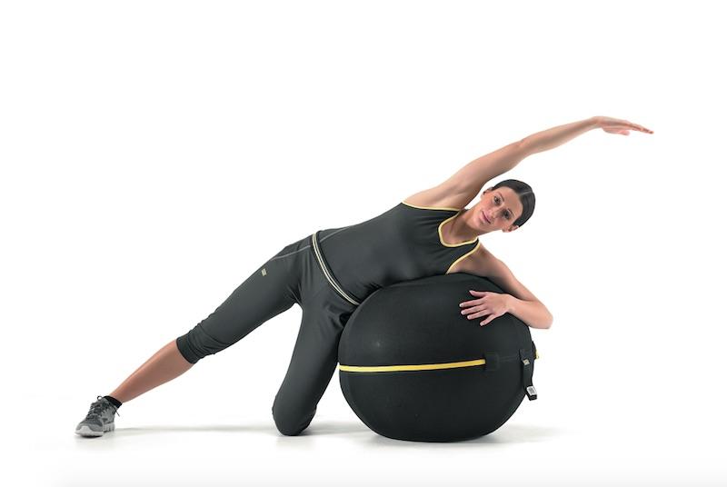 ウェルネスボール アクティブシッティング 55cmに体の側面をのせエクササイズしている女性
