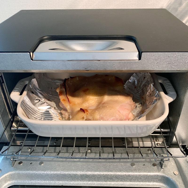 鶏もも肉をオーブンに入れている