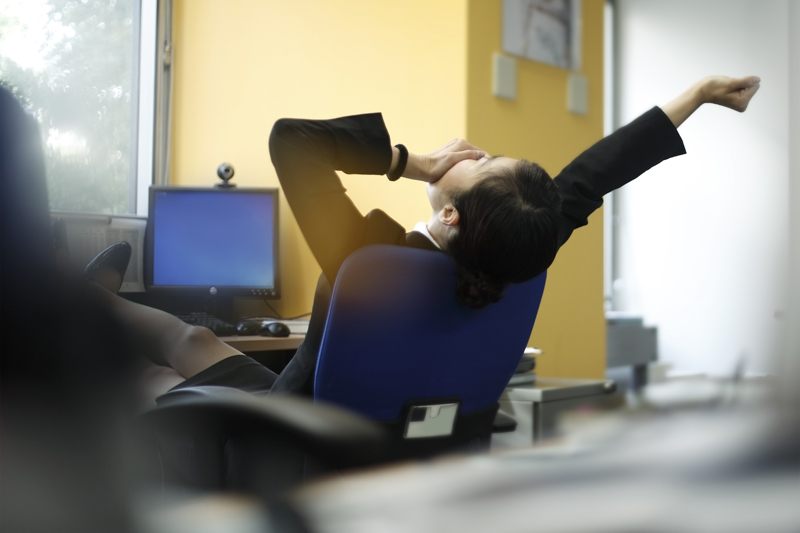 椅子にもたれてあくびと伸びをする女性