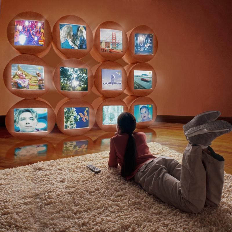 寝転んでたくさんの画面を観ている人